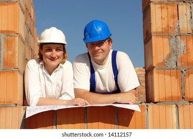 Couple wearing hard hats posing in their future house window opening resting on building plan
