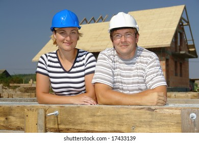 Couple wearing hard hats posing over unfinished house
