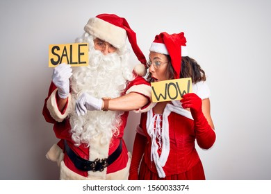 Couple wearing Santa costume holding wow and sale banner over isolated white background Looking at the watch time worried, afraid of getting late