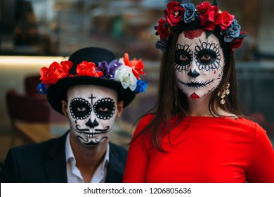 A couple, wearing skull make-up for. All souls day. Boy and girl sugar skull makeup.painted for halloween sit in a cafe. dead in the city. zombie walk.day of the dead holiday in mexico