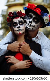 A couple, wearing skull make-up for. All souls day. Boy and girl sugar skull makeup.painted for halloween standing on the street. dead in the city. zombie walk.day of the dead holiday in mexico
