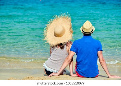 Couple wearing straw sun hat on beach. Summer vacation portrait. Sithonia, Greece.