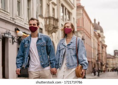 Couple wearing trendy fashionable protective masks, denim jackets, walking in empty street of European city during quarantine of coronavirus outbreak. Copy space for text