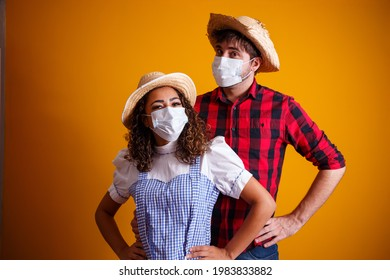 couple wearing typical clothes for the Festa Junina (Junina Party) and protection mask to prevent COVID-19.