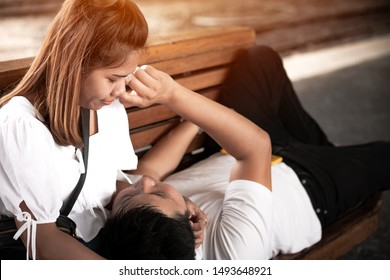 Couple wearing a white shirt sitting on a bench while waiting for the train