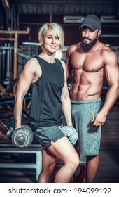Couple of well trained bodybuilder with dumbbells