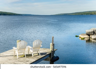 Couple of White Chairs on a Pier Facing a Beautiful Lake. Finger Lakes, Upstate New York