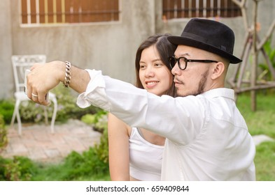 couple in white cloth taking selfie with smartphone