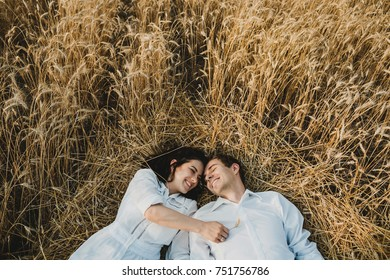 Couple in white looks gorgeous lying on golden field