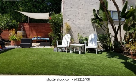 a couple of white outdoor chairs in the yard