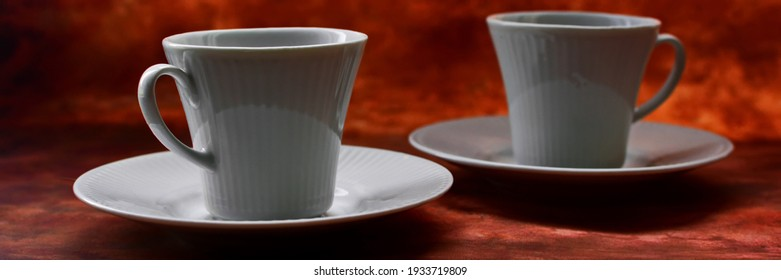 Couple of white porcelain coffee cups on saucers on brown background. Widescreeen panoramic view