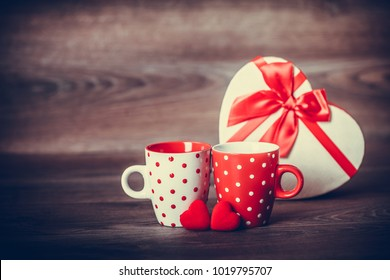Couple white and red cups with decoration by red hearts and gift in a box on wooden table. Valentine's day celebration concept. Copy space.
