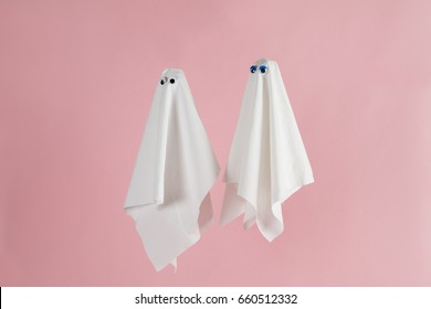 Couple of white sheet ghost with doll's eyes isolated on a pink background. Minimal pop still life photography