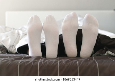 Couple in white socks lying in bed. Lovers together in the morning.