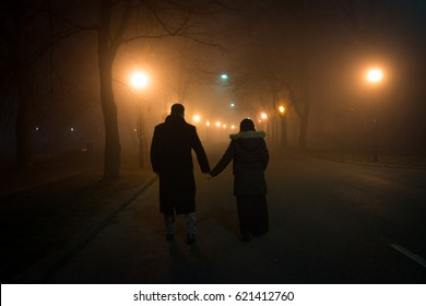 Couple wife and husband walking down the night street