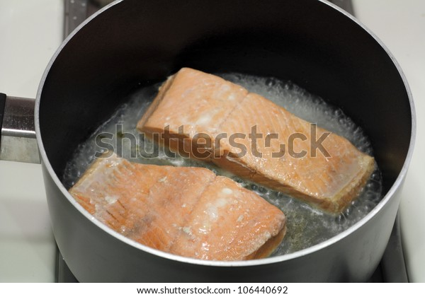 A couple of wild salmon fillets being cooked in a small amount of water in a saucepan on a stove top.