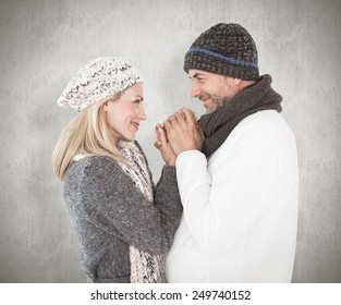 Couple in winter fashion embracing against weathered surface