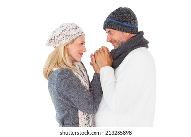 Couple in winter fashion embracing on white background