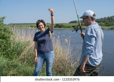 Couple woman and man fishing standing on lakeshore