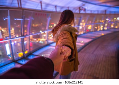 Couple woman and man follow holding hands in oriental pearl TV tower on night  background. Love and travel lifestyle concept.