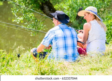 Couple, woman and man, sitting at river side with fishing rods angling for sport