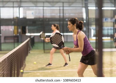 couple of women playing paddle tennis in indoor court