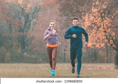 Couple in wonderful fall landscape running for better fitness towards the camera
