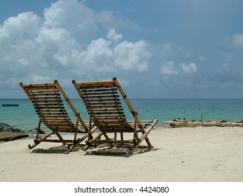 A couple of wooden deck chairs on white sand