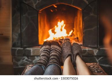 Couple in wool socks warming by cozy fire. Romantic winter eveni