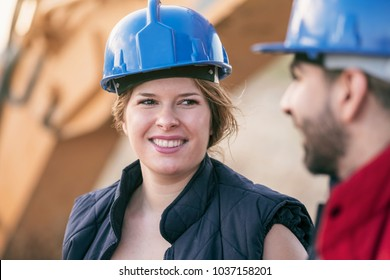 Couple of workers have relax time near to backhoe machine, focus in worker woman