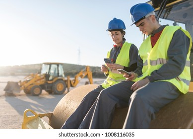 Couple of workers taking a break in their job and looking telephone on steamroller bulldozer