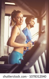 Couple working exercise on treadmill. Focus is on woman. Looking at camera.
