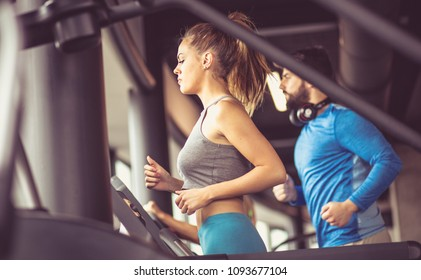 Couple working exercise on treadmill.