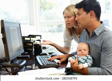 Couple working in home office with baby