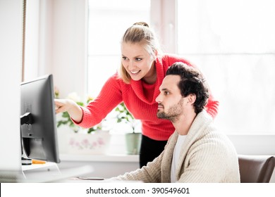 Couple working in home office with phone and computer