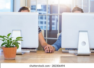 Couple working on computers and holding hands in the office