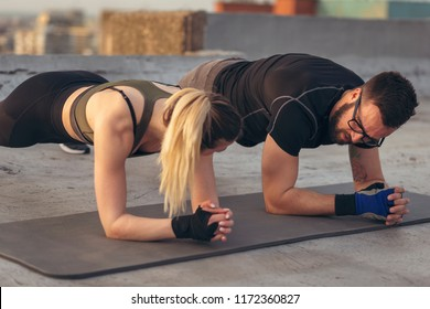 Couple working out on a building rooftop terrace, doing a plank exercise. Focus on the man