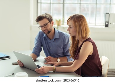 Couple working together in an office sitting at a laptop computer reading the screen with serious expressions