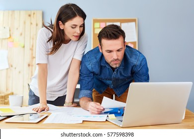 Couple working together at small office with laptop and documents