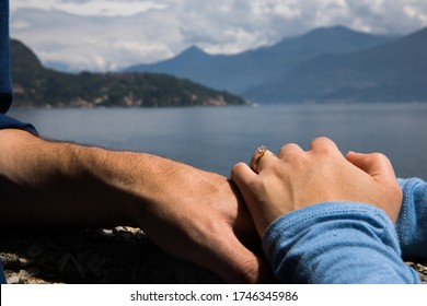 Couple. You can see the hands touching each other. Sensually.Water and mountains in the background.