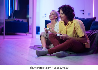 Couple of young adults playing video games at home. Emotional diverse gamers holding joysticks and compete in intense video game on gaming console.
