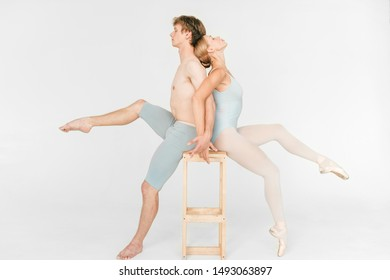 Couple of young and athletic ballet dancers sitting on chair back to back over white studio background