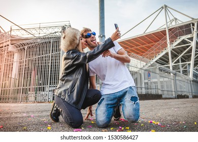 couple of young beautiful lovers take a selfie on the large square of a stadium