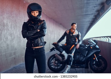Couple of young bikers is relaxing in quiet tunnel with their motobike. Girl is wearing helmet. Man is sitting on the bike behide her.