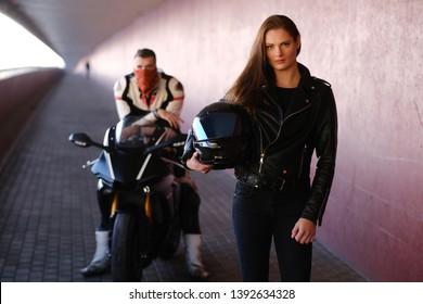 Couple of young bikers is relaxing in quiet tunnel with their motobike. Girl is holding helmet. Man is sitting on the bike behide her.