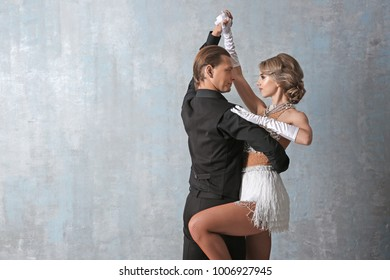 Couple of young dancers on color background
