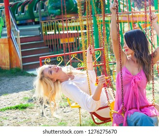 couple of young fashion girls have fun on flying carousel  in amusement park summer day