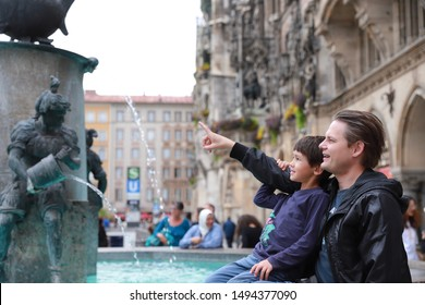 A couple of young father and little boy traveling together at Marienplatz town hall of Munich city. Father pointing finger showing something to his son with smiling face. Happy family travel concept