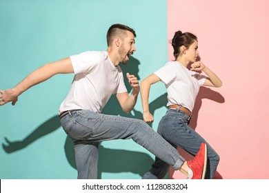 A couple of young funny and happy man and woman dancing hip-hop at studio or running on blue and pink trendy color background. Human emotions, youth, love and lifestyle concept