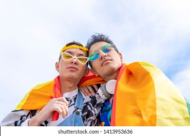 couple of young gay men in love smiling with pride flag. concept and equality of sexes